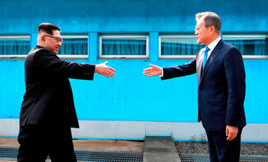 North Korean leader Kim Jong Un, left, prepares to shake hands with South Korean President Moon Jae-in over the military demarcation line at the border village of Panmunjom in the Demilitarized Zone on April 27, 2018.
