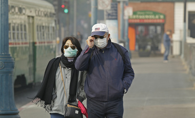 a couple walks through San Francisco wearing masks to protect from smoke and haze after wildfires