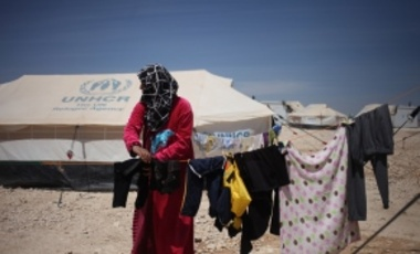 A Syrian woman hangs laundry in front of her family tent at the Zaatari Refugee Camp, in Mafraq, Jordan, Tuesday April 22, 2014.