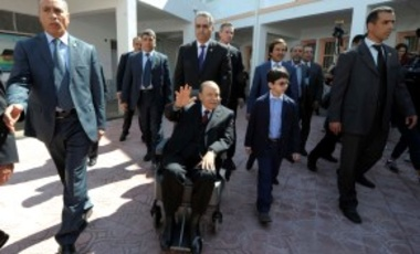 President Abdelaziz Bouteflika, centre, in a wheelchair, waves as he leaves after voting in the presidential elections in Algiers, Thursday, April 17, 2014.