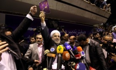Iranian presidential candidate Hasan Rouhani, center, holds up a leaflet showing a key, the symbol of his campaign, during a rally in Tehran, Iran, Saturday, June 8, 2013.