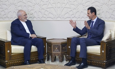 In this photo released by the Syrian official news agency SANA, Syrian President Bashar Assad, right, speaks with Iranian Foreign Minister Mohammad Javad Zarif in Damascus, Syria, Monday, Sept 3, 2018.
