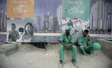 Migrant laborers working in the construction industry wait for their buses at the end of the working day in the Dubai Marina area, May 1, 2006 in Dubai, UAE. Migrant laborers are more than 2/3 of Dubai's population.