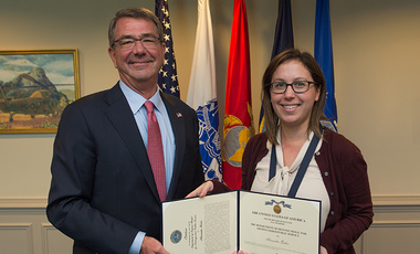Sasha Baker receives the Department of Defense medal for distinguished public service from Ash Carter.