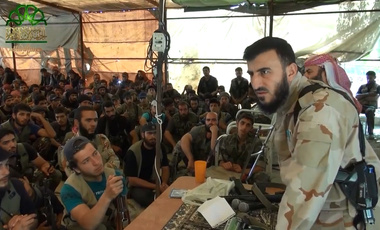 Zahran Alloush, leader of Jaysh al-Islam, speaks to his group's fighters before a battle with Islamic State in Mayda'a, Syria, July 2014