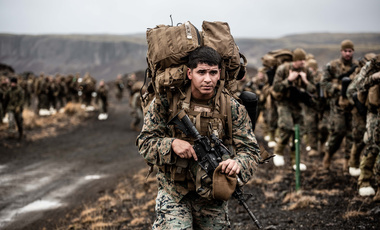 A U.S. Marine carries cold weather equipment as he begins to march across the Icelandic terrain in preparation for NATO's Trident Juncture 2018 exercise, October 19, 2018.
