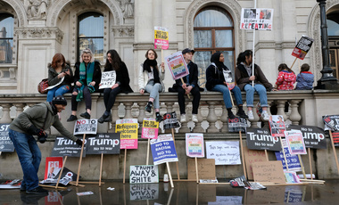 Anti-Trump protesters taking a rest in Whitehall during the London march against Trump's immigration ban.