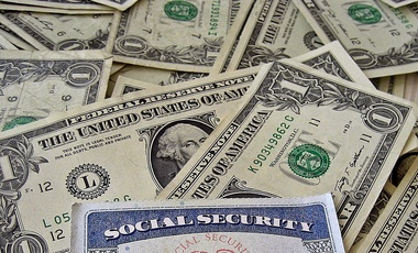 A Social Security card on a bed of money. (Flickr/401(K) 2012)