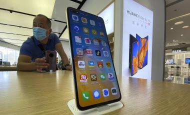 Photo of a visitor to a Huawei retail store stands near a Huawei smartphone displaying a variety of apps in Beijing on Tuesday, Sept. 8, 2020.