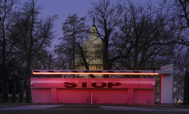 An illuminated traffic barrier is seen on the Capitol grounds before sunrise in Washington, Monday, March 8, 2021.