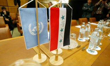 The U.N., left, and Iraqi flags sit on the table of the conference hall prior to the talks on details for a return of the U.N weapons inspectors to Iraq at the IAEA headquarters in Vienna, Austria, Monday, Sept. 30, 2002.