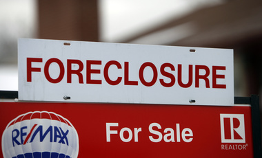 A foreclosure sign sits on top of a sale placard outside a home on the market in the south Denver suburb of Littleton, Colorado, on Tuesday, December 23, 2008.