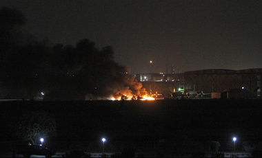 A building at a Pakistani naval aviation base burns during an attack by a substantial group of well-armed, well-trained militants, apparently with insider help, in May 2011. Nuclear weapons and materials must be protected against comparable adversary capabilities and tactics (AP Photo/Shakil Adil).
