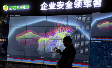 A worker is silhouetted against a computer display showing a live visualization of the online phishing and fraudulent phone calls across China during the 4th China Internet Security Conference in Beijing. Aug. 16, 2016 (Ng Han Guan/Associated Press, File). Keywords: China, cyberattack