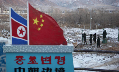 "In this Dec. 8, 2012 photo, Chinese paramilitary policemen build a fence near a concrete marker depicting the North Korean and Chinese national flags with the words ""China North Korea Border"" at a crossing in the Chinese border town of Tumen in eastern China's Jilin province. (AP Photo/Ng Han Guan, File)"