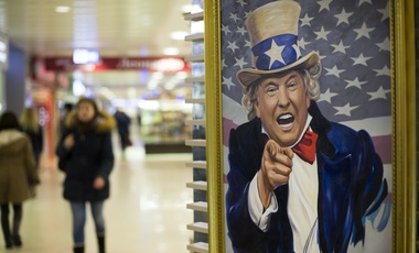 People walk past a caricature picture of U.S. President Donald Trump on sale in a shopping mall in Moscow on Wednesday, March 22, 2017. (AP Photo/Alexander Zemlianichenko)