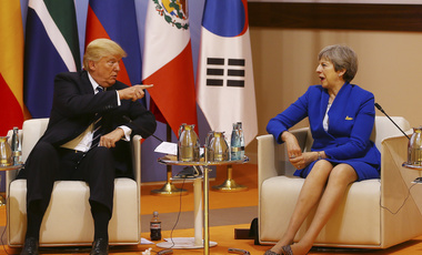 "US President Donald Trump, left, gestures as he talks with Britain's Prime Minister Theresa May, right, at the start of the ""retreat meeting"" on the first day of the G-20 summit in Hamburg, Germany on July 7, 2017 (Turkish Presidency Press Service via AP, Pool)."