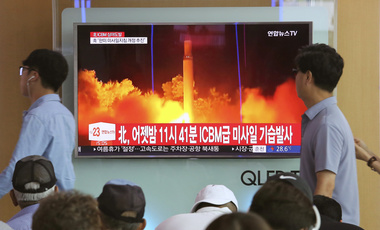 "FILE - In this Saturday, July 29, 2017 photo, People watch a TV news program showing an image of North Korea's latest test launch of an intercontinental ballistic missile (ICBM), at the Seoul Railway Station in Seoul, South Korea. South Korea's latest leader Moon Jae-in told U.S. President Donald Trump he's happy to talk about North Korea's ICBM test but after his vacation. It might seem like an oddly timed break for a relatively new president during his country's biggest crisis. The signs read ""North Korea"