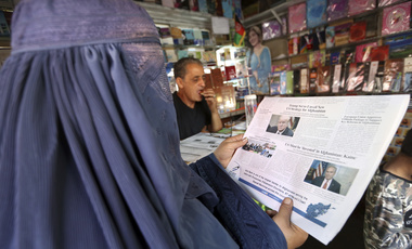 "An Afghan woman reads a local newspaper with photo of the U.S. President Donald Trump in Kabul, Afghanistan, Tuesday, Aug. 22, 2017. Reversing his past calls for a speedy exit, Trump recommitted the United States to the 16-year-old war in Afghanistan Monday night, declaring U.S. troops must ""fight to win."" (AP Photo/Rahmat Gul)"