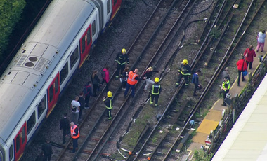 Emergency workers help people disembark a train near the Parsons Green Underground Station after an explosion in London on Friday, Sept. 15, 2017. (Pool via AP)