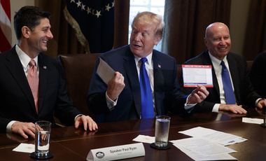 President Donald Trump holds an example of what a new tax form may look like during a meeting on tax policy with Republican lawmakers in the Cabinet Room of the White House on Nov. 2, 2017 (AP Photo/Evan Vucci).