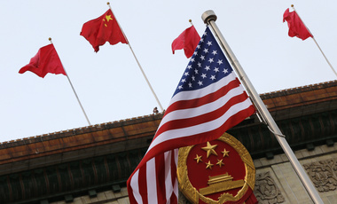 An American flag is flown next to the Chinese national emblem and flags during a welcome ceremony for visiting U.S. President Donald Trump outside the Great Hall of the People in Beijing. November 9, 2017 (Andy Wong/Associated Press).