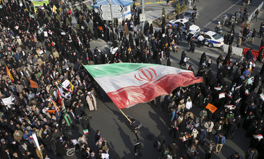 In this photo provided by Tasnim News Agency, a demonstrator waves a huge Iranian flag during a pro-government rally in the northeastern city of Mashhad, Iran, on Jan. 4, 2018 (Nima Najafzadeh/Tasnim News Agency via AP).