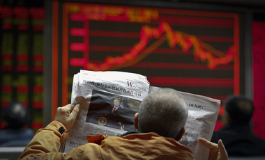 A man reads a newspaper at a brokerage house in Beijing.