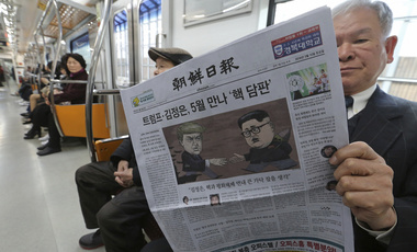 A passenger reads a newspaper with headline of a planned summit meeting between North Korean leader Kim Jong Un and U.S. President Donald Trump, left, at subway train in Seoul, South Korea. March 10, 2018 (Ahn Young-joon/Associated Press). Keywords: South Korea, North Korea, Trump, Kim Jong-Un