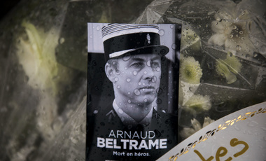 A photo of Lieutenant Colonel Arnaud Beltrame placed on a bunch of flowers at the main gate of the Police headquarters in Carcassonne, France, following an attack on a supermarket in Trebes in the south of the country. March 24, 2018 (Emilio Morenatti/Associated Press). Keywords: Arnaud Beltrame, France