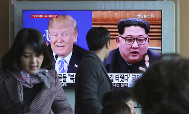 Photo of a man watching a screen in Seoul that shows photos of Donald Trump and Kim Jong-un.