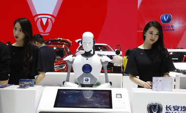 "A robot assists receptionist at the booth of a Chinese automaker at the China Auto 2018 show in Beijing, China on April 26, 2018. Under President Xi Jinping, the ""Made in China 2025"" program aims to develop high-tech industry in China. (AP Photo/Ng Han Guan, File)"