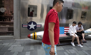 A man walks past a rocket shaped bench with an American flag outside of a U.S. apparel shop in Beijing, China on Friday, July 6, 2018.