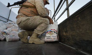 Russian officer prepares to distribute a food aid for local residents in the outskirts of Damascus