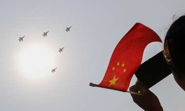 A woman holding a flag films PLA Air Force jets as they fly in formation during a parade to commemorate the 70th anniversary of the founding of the People's Republic of China in Beijing, Tuesday, Oct. 1, 2019.