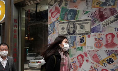 People walk by a money exchange shop in Hong Kong.