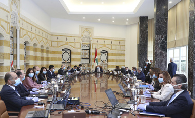 In this photo released by the Lebanese Government, President Michel Aoun, center, and government ministers wear masks to help protect themselves from the coronavirus, while attending a cabinet meeting at the presidential palace in Baabda, east of Beirut.
