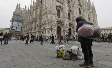 A homeless stands at the Duomo square, in Milan, Italy on Wednesday, Oct. 10, 2012. Italy's per capita GDP in 2018 is about 8% below its level in 2007, the year before the global financial crisis triggered the Great Recession. (Luca Bruno/AP Photo)