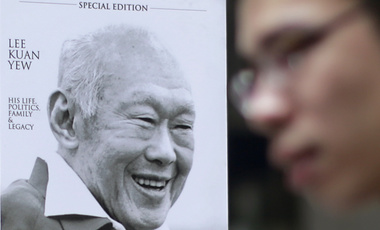"A newspaper vendor stands in front of a poster of the late Lee Kuan Yew in the financial district of Singapore on Monday, March 23, 2015. Singaporeans wept and world leaders paid tribute Monday as the Southeast Asian city-state mourned the death of its founding father Lee Kuan Yew. The government announced that Lee, 91, ""passed away peacefully"" several hours before dawn at Singapore General Hospital. (AP Photo/Wong Maye-E)"