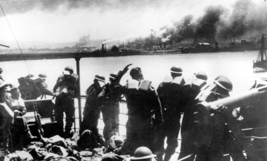 Troops of the British Expeditionary Force view the Nazi bombardment of Dunkirk from a transport after their evacuation from the French coast during World War II. The emergency evacuation of Allied forces, known as Operation Dynamo, took place between May 29 and June 3, 1940. (AP Photo)