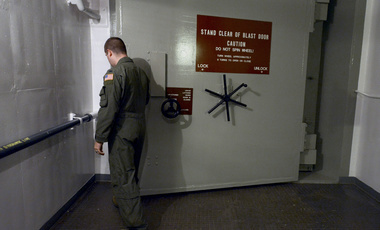 A lieutenant opens a blast door at a U.S. ICBM launch control facility.