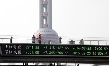 Photo of people crossing bridge in Shanghai that shows stock prices.
