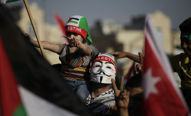 A man wears a Guy Fawkes mask and carries his daughter during a celebration by the Muslim Brotherhood movement to declare victory of Gaza and Hamas against Israel, in Amman, Jordan, Friday, Aug. 29, 2014. (AP Photo/Mohammad Hannon)