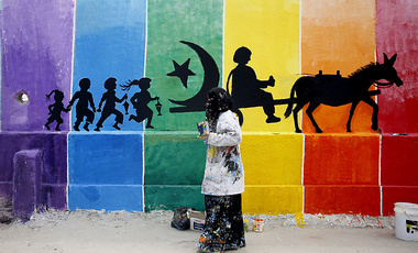 A Palestionian artist works on a mural of a school run by the United Nations Relief and Works Agency (UNRWA) in the Shati Refugee Camp west of Gaza City, Tuesday, May 10, 2016. The UNRWA assigned 140 local artists to draw graffiti and murals on all the agency's premises in the Gaza Strip as part of a campaign to boost artistic and social values in the territory. (AP Photo/Hatem Moussa)