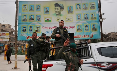 In this photo taken on Wednesday, March 28, 2018, members of the Kurdish internal security forces stand on their vehicle in front of a giant poster showing portraits of fighters killed fighting against the Islamic State group, in Manbij, north Syria. Manbij, a mixed Arab and Kurdish town of nearly 400,000, was liberated from Islamic State militants in 2016 by the YPG fighters with backing from U.S-led coalition airstrikes. With Turkey's threats, the town has become the axle for U.S. policy in Syria, threate
