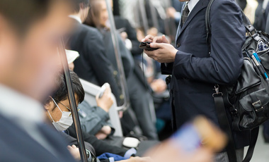 Commuters use mobile phones in Tokyo, Japan.
