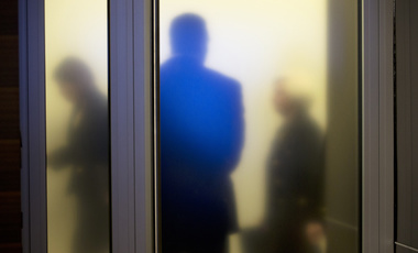 Federal Reserve employees walk past a frosted glass window on the way to a news conference, September 17, 2015.