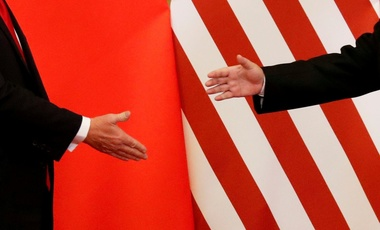 A visiting U.S. President Donald Trump reaches out to greet his Chinese counterpart Xi Jinping, November 9, 2017.