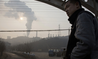 a man looks up near smoke spewing from a chimney near the Jiujiang steel and rolling mills in Qianan