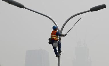 A worker refurbishes a lamp post in Beijing blanketed by heavy smog